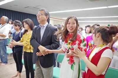 民族衣装「アオザイ」を着たベトナム出身実習生と市民が歌の振付に合わせて握手