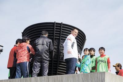 子どもたちが室伏氏と一緒に聖火台...