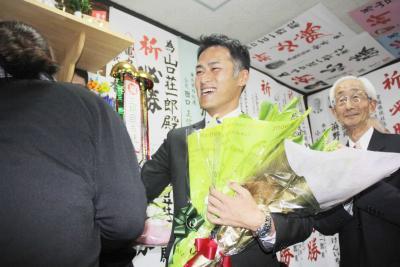 支持者から花束を受け取る山口さん