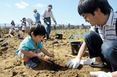 成長を願って苗木を植える親子