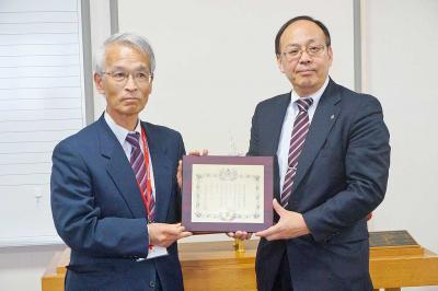 関係者から受章記念の盾を受け取った瀧田雅樹校長(右、昨年3月27日)