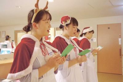 病棟の廊下でクリスマス曲を歌う学生